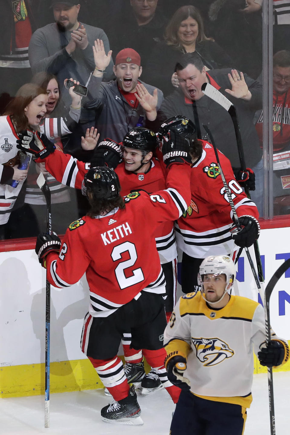 Chicago Blackhawks left wing Alex DeBrincat (12) celebrates with defenseman Duncan Keith (2) and left wing Brandon Saad after scoring the winning goal as Nashville Predators right wing Viktor Arvidsson reacts on the ice during the overtime period of an NHL hockey game in Chicago, Friday, Feb. 21, 2020. (AP Photo/Nam Y. Huh)
