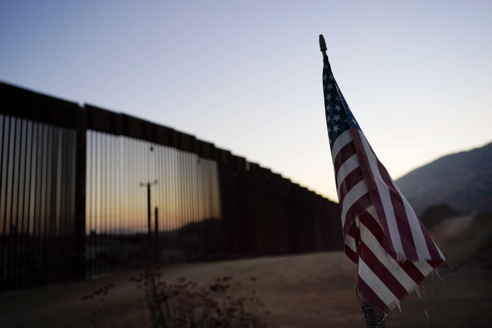 "A flag sits just north of a new section of the border structure, behind, Thursday, Sept. 24, 2020, near Tecate, Calif. President Donald Trump's reshaping of U.S. immigration policy may be most felt in his undoing of asylum. With immigration laws temporarily suspended at the border during the pandemic, people who enter the U.S. illegally are immediately ""expelled"" without even a piece of paper to record the incident. (AP Photo/Gregory Bull)"