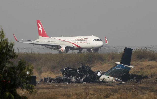 <p>Remains of Bangladesh's US-Bangla Flight BS211 lies on the ground as a plane takes off from Tribhuvan International Airport in Kathmandu, Nepal, March 13, 2018. (Photo: Niranjan Shreshta/AP) </p>