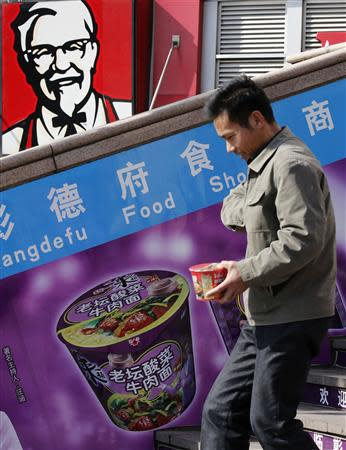 A man holding an instant cup noodle pack walks past a logo of KFC in Beijing October 23, 2013. REUTERS/Kim Kyung-Hoon