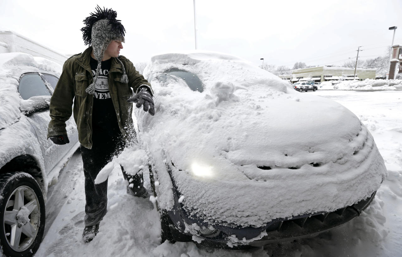 Noah Nichols, of Des Moines, Iowa, cleans snow off his car, Thursday, Dec. 20, 2012, in Des Moines, Iowa. The first widespread snowstorm of the season began a slow crawl across the Midwest on Thursday with some areas receiving as much as 15 inches of snow. (AP Photo/Charlie Neibergall)