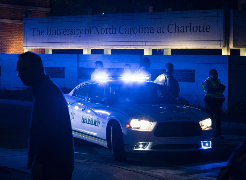 FILE - In this April 30, 3019 file photo, police secure the main entrance to UNC Charlotte after a fatal shooting at the school, in Charlotte, N.C. Most of the students who commit deadly school attacks were bullied, had a history of disciplinary trouble and their behavior concerned others, but it wasn't reported. That's according to a comprehensive study by the U.S. Secret Service's National Threat Assessment Center of 41 school attacks since the 1999 Columbine High School Shooting.(AP Photo/Jason E. Miczek)