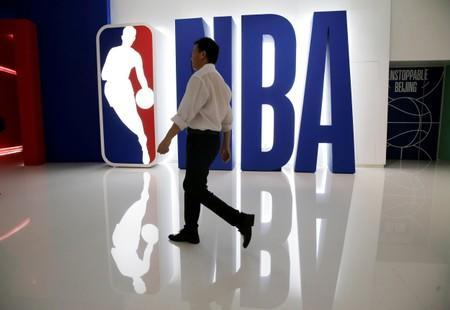 A man walks past an NBA logo at an NBA exhibition in Beijing