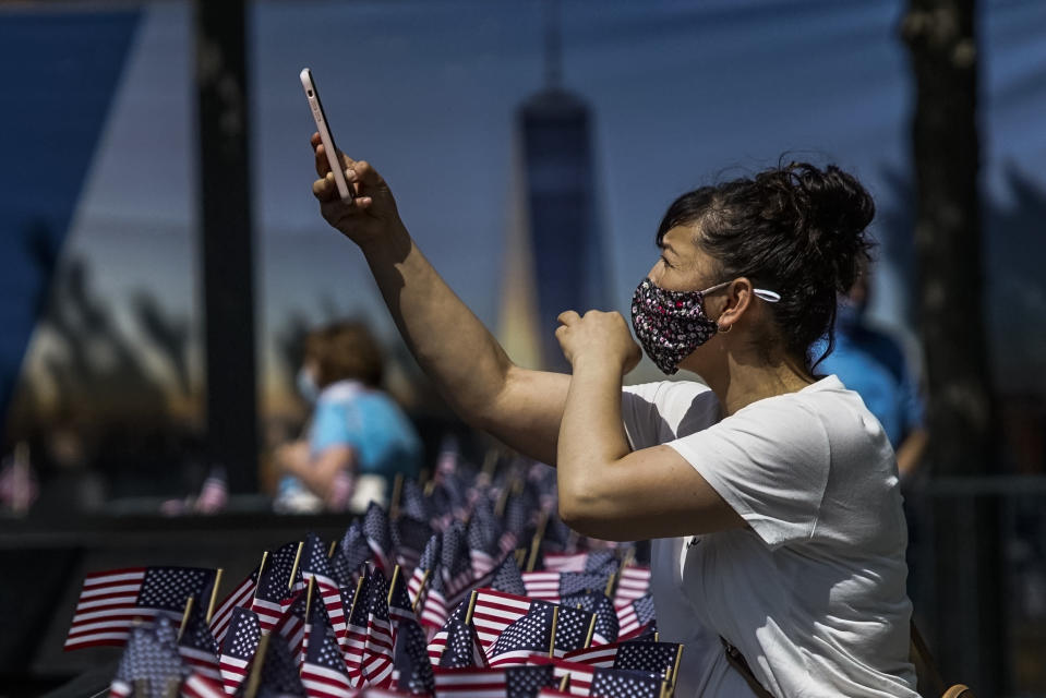 A woman takes pictures with her phone as people visit the 9/11 Memorial Plaza during its reopening after having been closed for more than three months amid the coronavirus pandemic, Saturday, July 4, 2020, in New York. (AP Photo/Eduardo Munoz Alvarez)