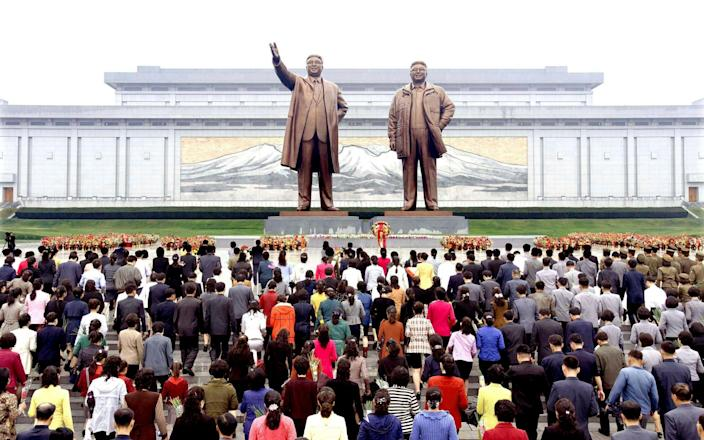 Floral tributes are paid to the statues of North Korea founder Kim Il Sung and late leader Kim Jong Il - REUTERS