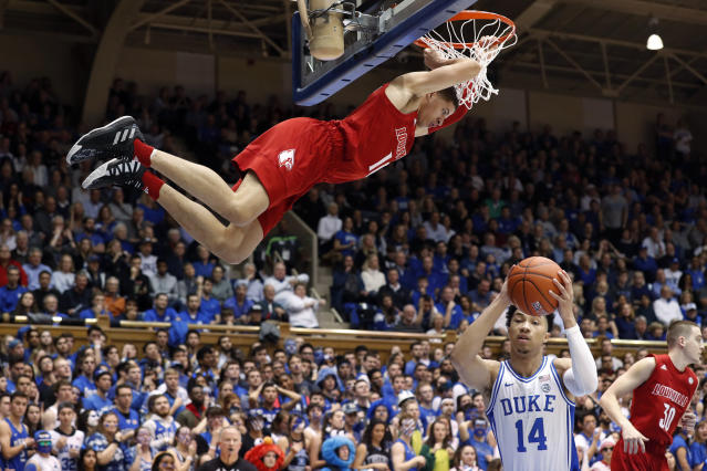 Louisville guard Samuell Williamson hangs from the rim after a dunk over Duke guard Jordan Goldwire (14) during the first half of an NCAA college basketball game in Durham, N.C., Saturday, Jan. 18, 2020. (AP Photo/Gerry Broome)