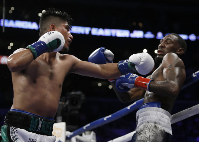 Mikey Garcia, left, hits Robert Easter Jr. with a left during the 12th round of their WBC and IBF lightweight title bout in Los Angeles, Saturday, July 28, 2018. Garcia won by unanimous decision. (AP Photo/Alex Gallardo)