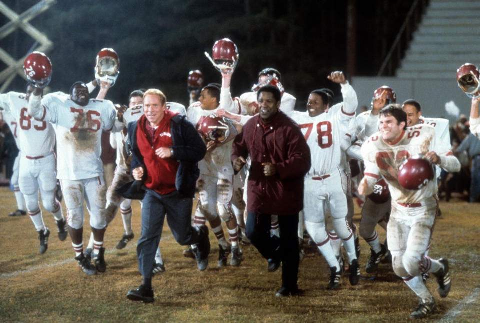 Will Patton and Denzel Washington run out onto the field in a scene form the film 'Remember The Titans', 2000. (Photo by Buena Vista/Getty Images)