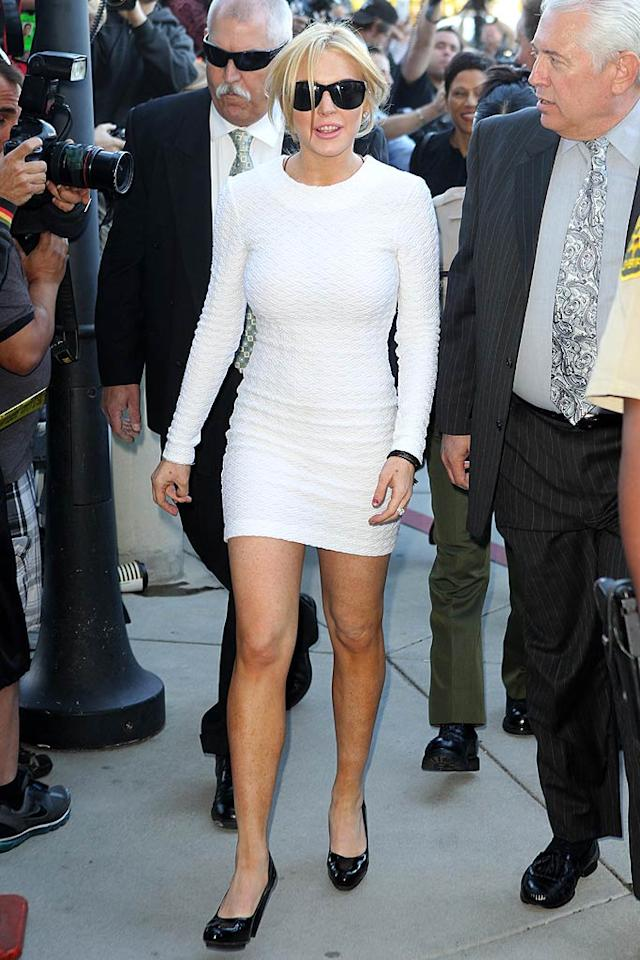 """A day after she was charged with one count of felony grand theft for stealing a $2,500 necklace, Lindsay Lohan jumped on Twitter and claimed that she had never been """"raised to lie, cheat, or steal."""" Fine, but who raised her to wear such inappropriate outfits to court? Our guess? Her wannabe star/momager, Dina Lohan. Splash News/<a href=""""http://www.splashnewsonline.com"""" target=""""new"""">Splash News</a> - February 9, 2011"""