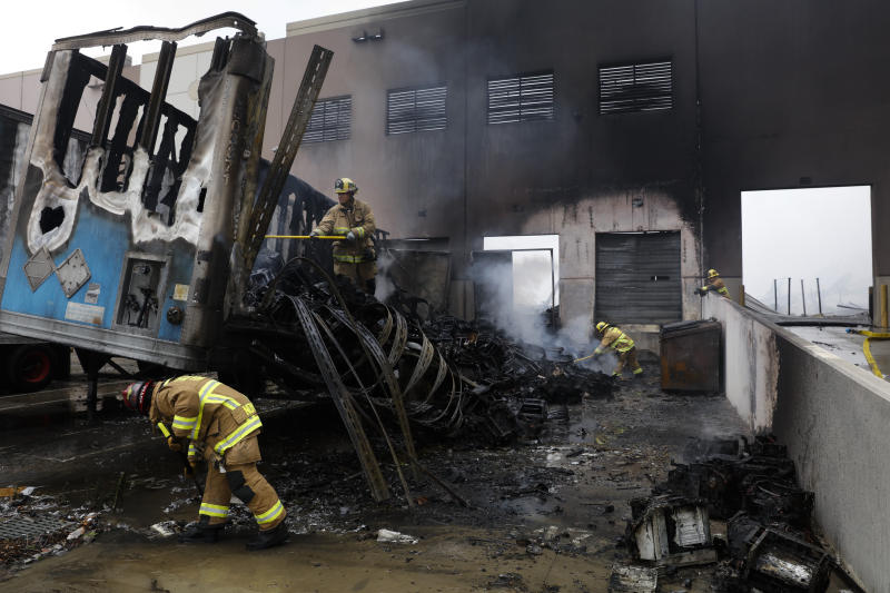 Firefighters put out hot spots at a warehouse destroyed in a fire, Friday, June 5, 2020, in Redlands, Calif. The fire destroyed the Southern California distribution facility that was used to ship items to Amazon customers but authorities said employees got out and there were no reports of injuries. (AP Photo/Jae C. Hong)