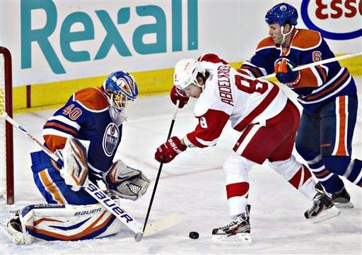 Detroit Red Wings' Justin Abdelkader (8) is stopped by Edmonton Oilers goalie Devan Dubnyk (40) as Ryan Whitney (6) defends during the second period of an NHL hockey game Friday, March 15, 2013, in Edmonton, Alberta. (AP Photo/The Canadian Press, Jason Franson)