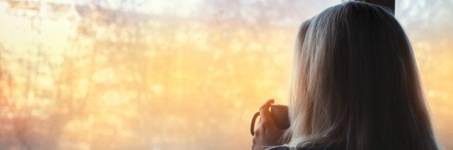 Woman standing by the window, with coffee cup.