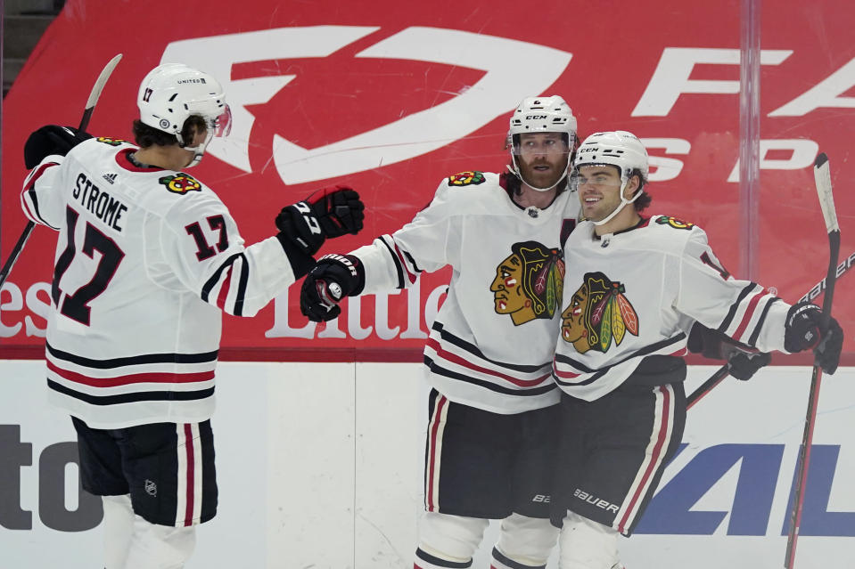 Chicago Blackhawks center Dylan Strome (17), defenseman Duncan Keith (2) and left wing Alex DeBrincat (12) celebrate a goal by Keith during the first period of an NHL hockey game against the Detroit Red Wings, Thursday, April 15, 2021, in Detroit. (AP Photo/Carlos Osorio)