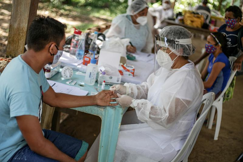 MANAUS, BRAZIL - MAY 29: A nurse performs a coronavirus (COVID-19) test to a resident of the riverside community of Belavista do Jaraqui, in Negro river, about one hour by boat from Manaus, on May 29, 2020 in Brazil. According to the Amazonas Health Surveillance Foundation (FVS-AM) 20,377 positive cases of coronavirus were detected in the Amazonas state cities. (Photo by Andre Coelho/Getty Images)
