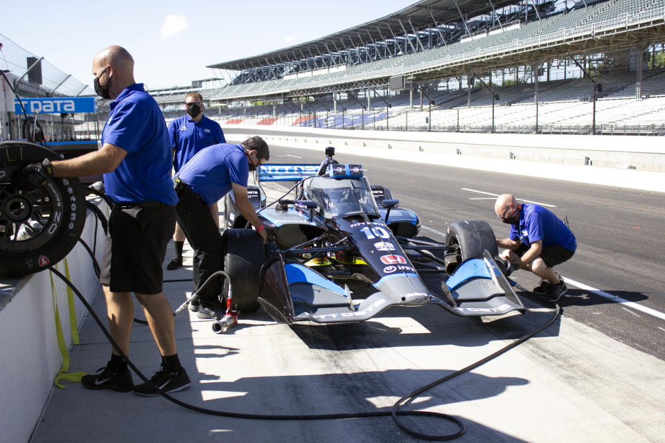 In this image provided by Jimmie Johnson Racing II, Inc., crew members change tires as seven-time NASCAR champion Jimmie Johnson, sits in an IndyCar during testing with Chip Ganassi Racing on the road course at Indianapolis Motor Speedway, Tuesday, July 28, 2020, in Indianapolis. Johnson is interested in competing in the IndyCar Series when he retires from full-time NASCAR competition at the end of this season. (Jimmie Johnson Racing II, Inc. via AP)