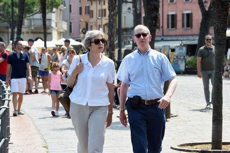 Britain's Prime Minister Theresa May and her husband Philip walk on the waterfront whilst on vacation in Desenzano del Garda