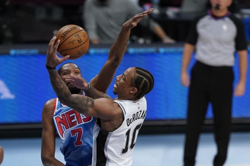 San Antonio Spurs' DeMar DeRozan, right, drives past Brooklyn Nets' Kevin Durant as James Harden, left, watches during the first half of an NBA basketball game Wednesday, May 12, 2021, in New York. (AP Photo/Frank Franklin II)