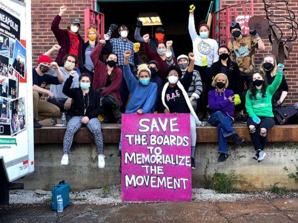 PHOTO: Kenda Zellner-Smith, center left, and Leesa Kelly, center right, pose with a group of activists. Protest art has been collected by Save the Boards to Memorialize the Movement. (Courtesy of Save the Boards to Memorialize the Movement)