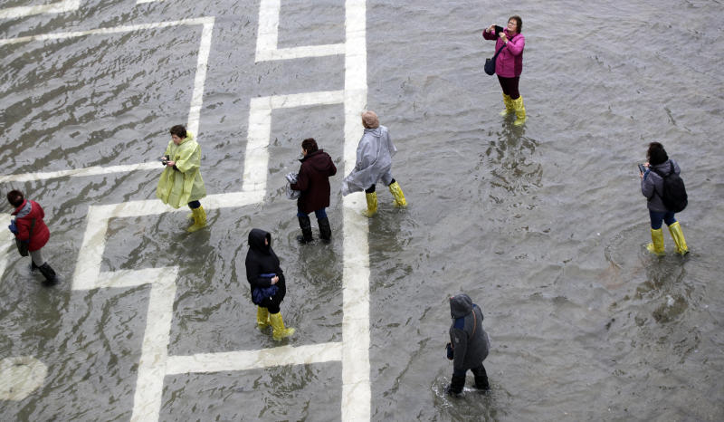 People walk in a flooded St. Mark's Square, in Venice, Italy, Tuesday, Nov. 12, 2019. (Photo: Luca Bruno/AP)