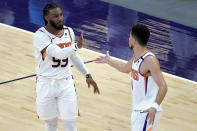 Phoenix Suns forward Jae Crowder (99) celebrates his three pointer with guard Devin Booker during the first half of an NBA basketball game against the Houston Rockets, Monday, April 12, 2021, in Phoenix. (AP Photo/Matt York)