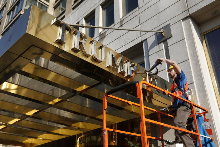 FILE - In this Wednesday, Nov. 16, 2016 file photo, a worker removes letters from the awning of a building formerly known as Trump Place in New York. Donald Trump's name is being stripped off three luxury apartment buildings after hundreds of tenants signed a petition saying they were embarrassed to live in a place associated with the Republican president-elect. (AP Photo/Seth Wenig, File)