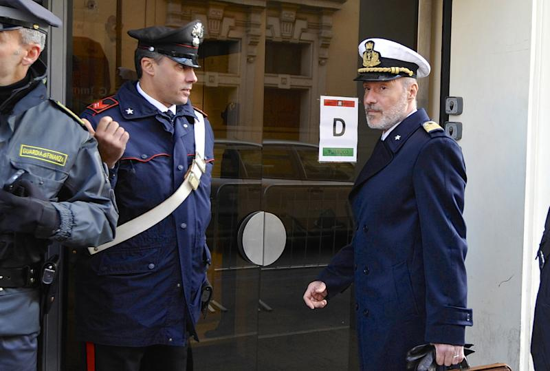 Coast Guard Capt. Gregorio De Falco, right, arrives at the Grosseto court, Italy, Monday, Dec. 9, 2013. A Italian Coast Guard official has testified that hundreds of people were still aboard the shipwrecked Costa Concordia when the commander abandoned the cruise liner in a lifeboat. Coast Guard Capt. Gregorio De Falco become a national hero after repeatedly ordering Francesco Schettino, the Concordia's commander on trial for manslaughter and abandoning ship, to return to the badly listing vessel. Schettino is also charged with causing the 2012 shipwreck by sailing too close to the Tuscan island of Giglio. A reef gashed the hull, water rushed in and 32 people died. (AP Photo/Giacomo Aprili)