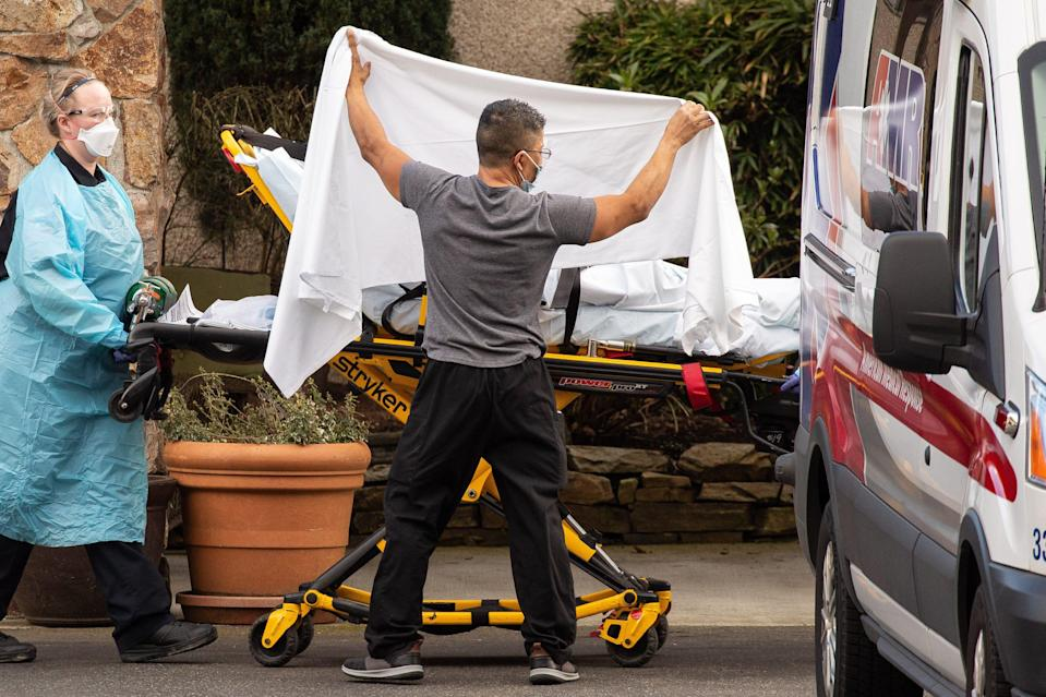 Health-care workers transport a patient into an ambulance at Life Care Center of Kirkland on Feb. 29, 2020, in Kirkland, Wash. Dozens of staff and residents at Life Care Center of Kirkland were reportedly exhibiting coronavirus-like symptoms.