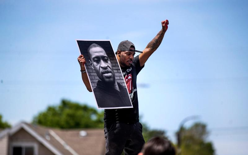 A protester in Minneapolis holds a photo of George Floyd - AP
