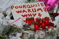 A sign asking why is seen amongst candles and flowers outside the Bataclan music hall following a series of shooting attacks on Friday in Paris, November 16, 2015. REUTERS/Christian Hartmann
