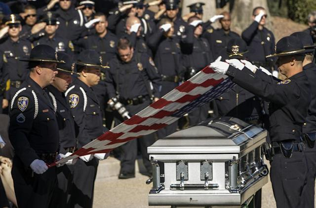 Riverside Police honor guard fold the flag from the coffin of Riverside Police officer Michael Crain, who was allegedly shot to death by accused killer and fired Los Angeles police officer, Christopher Dorner, as it arrives fro a committal service at the Riverside National Cemetery in Riverside, Calif., Wednesday, Feb. 13, 2013. (AP Photo/Damian Dovarganes)