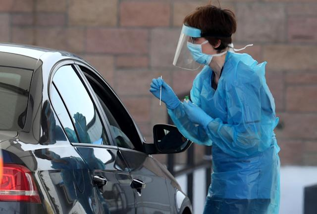 A nurse prepares to take a sample at a COVID 19 testing centre ahead of the new figures being released. (PA Images)