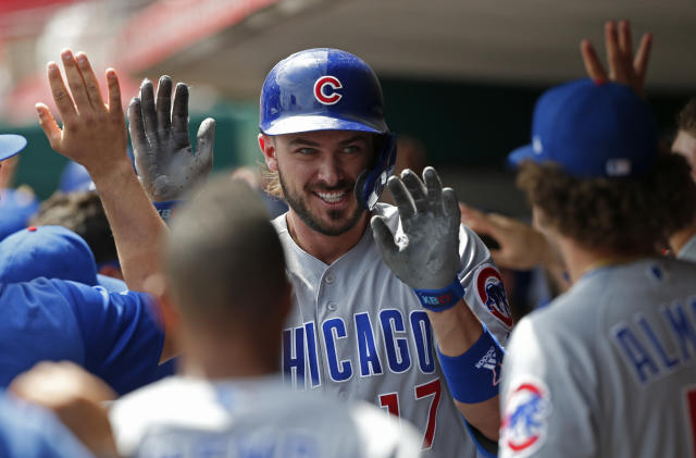 Chicago Cubs' Kris Bryant, center, celebrates a three-run home run off Cincinnati Reds relief pitcher Michael Lorenzen during the seventh inning of a baseball game, Sunday, Aug. 11, 2019, in Cincinnati. (AP Photo/Gary Landers)