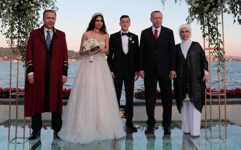 Arsenal's German midfielder Mesut Ozil (3rd L) and his fiance Amine Gulse (2nd L) standing next to Turkish President Recep Tayyip Erdogan (2nd R) and his wife Emine during their wedding ceremony at the Four Seasons Bosphorus Hotel in Istanbul,  - Credit: AFP