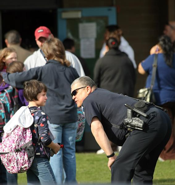 An Armin Jahr Elementary School student talks with a police officer in front of the school Wednesday, Feb. 22, 2012, in Bremerton, Wash. An 8-year-old girl was shot in the abdomen at the elementary school and one of her classmates was detained, authorities said. The injured third-grader was airlifted to Seattle's Harborview Medical Center. Authorities said a third-grade boy was being questioned and a firearm was found in a classroom. (AP Photo/Kitsap Sun, Larry Steagall)