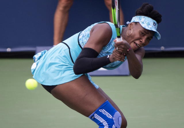 Venus Williams, of the United States, returns to Sorana Cirstea, of Romania, during the Rogers Cup women's tennis tournament, Thursday, Aug, 9, 2018 in Montreal. (Paul Chiasson/The Canadian Press via AP)