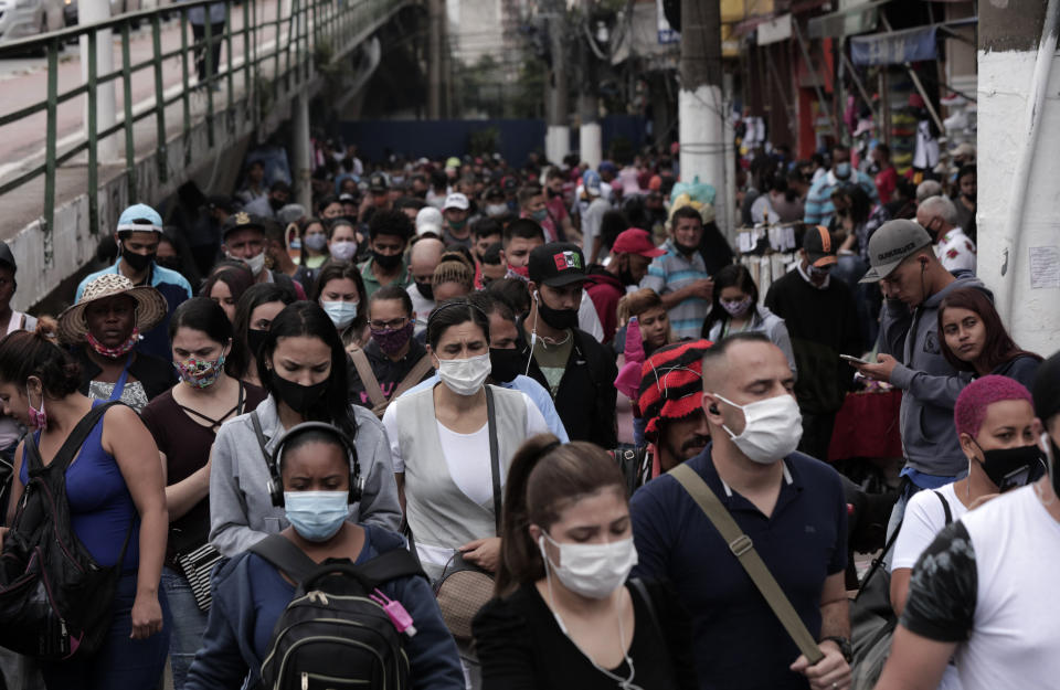 SAO PAULO, BRAZIL - DECEMBER 10: People wearing face masks walk the busy shopping streets of downtown Sao Paulo on December 10, 2020 in Sao Paulo, Brazil. According to the state of Sao Paulo, the risk of COVID-19 transmission is greater in December than in July during the first peak of the pandemic. (Photo by Rodrigo Paiva/Getty Images)