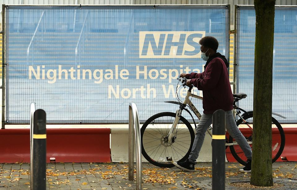 A cyclist wearing a face mask or covering due to the COVID-19 pandemic, pushes a bike past a barrier outside the NHS Nightingale Hospital North West field hospital, set up to provide more hospital capacity during the novel coronavirus pandemic, at Manchester Central Convention Complex in Manchester, northwest England on October 13, 2020. - The National Health Service (NHS) announced that three field hospitals across northern England, in Manchester, Sunderland and Harrogate, would be mobilised to accept new patients amid rising coronavirus infections. The British government faced renewed pressure on October 13 after indications it had ignored scientific advice three weeks ago for tougher restrictions to cut rising coronavirus infections. (Photo by Oli SCARFF / AFP) (Photo by OLI SCARFF/AFP via Getty Images)