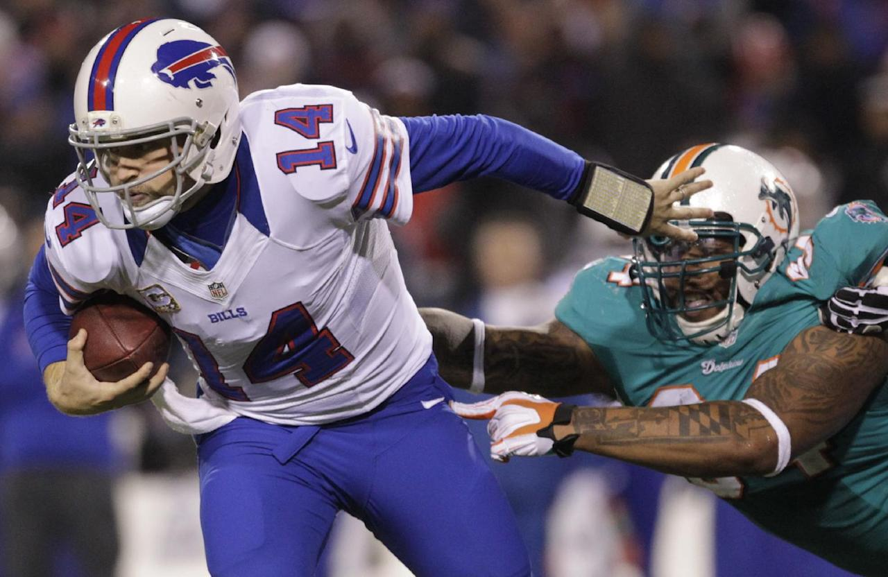 Buffalo Bills quarterback Ryan Fitzpatrick (14) breaks a tackle by Miami Dolphins defensive tackle Randy Starks (94) during the second half of an NFL football game on Thursday, Nov. 15, 2012, in Orchard Park, N.Y. (AP Photo/Bill Wippert)