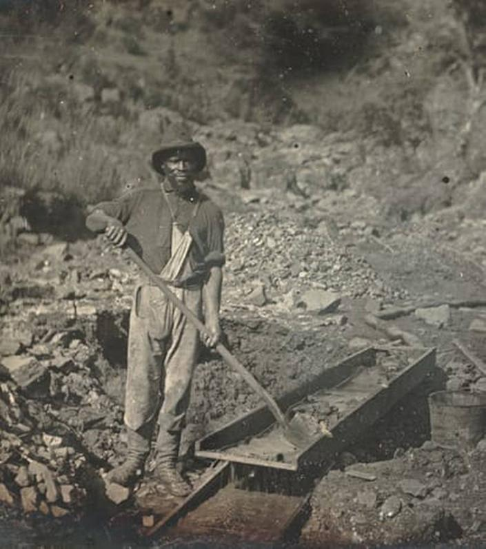 An unidentified Black miner works a sluice in Placer County, CA, likely near the Auburn Ravine in 1852 at the height of the Gold Rush. Downstream on the American River was an area now known as Negro Bar, where many Black miners worked.