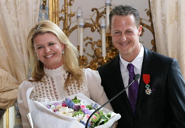 German Formula 1 pilot, Michael Schumacher poses with his wife Corinna after he was awarded with the French Legion of Honor by French Prime Minister Francois Fillon on April 29, 2010 at the Hotel Matignon in Paris. THOMAS COEX/AFP/GettyImages)