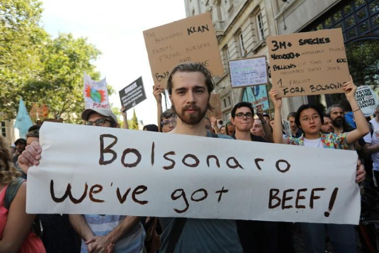 """Protesters with a banner that reads """"Bolsonaro we've got beef!"""" block a street at a climate change demonstration in London on August 23, 2019; Finland is now weighing a Brazilian beef ban over Amazon fires"""