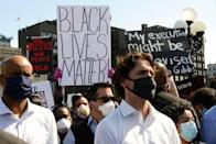 A protester holds up a Black Lives Matter sign behind Prime Minister Justin Trudeau as people take part in an antiracism protest on Parliament Hill in Ottawa on Friday, June 5, 2020.