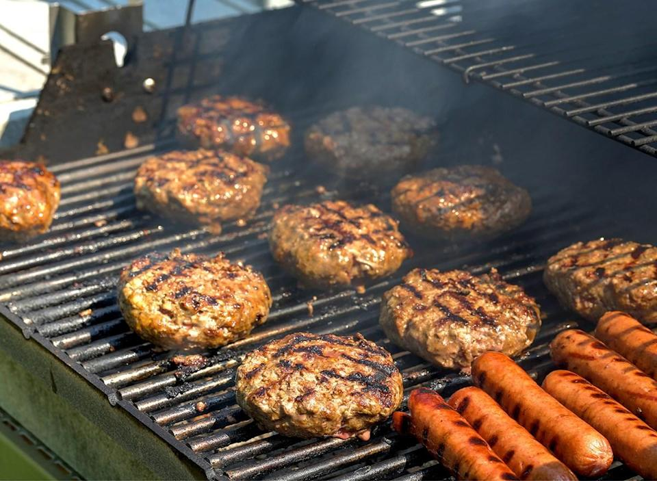 multiple burger patties and hot dogs on grill