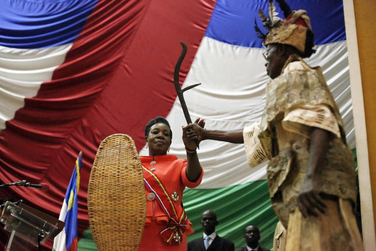 Central African Republic's interim President Catherine Samba-Panza, center, receives traditional gifts in the parliament building after taking the oath of office in Bangui, Central African Republic, Thursday Jan. 23, 2014. Samba-Panza pledged to bring peace and unity to the anarchic country as looters in the streets pillaged Muslim neighborhoods in the latest sign of escalating sectarian tensions.(AP Photo/Jerome Delay)