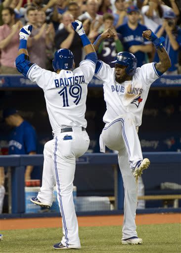 Toronto Blue Jays' Jose Reyes, right, congratulates teammate Jose Bautista after the two scored on Bautista's home run off Tampa Bay Rays starting pitcher David Price during the third inning of a baseball game in Toronto on Friday, July 19, 2013. (AP Photo/The Canadian Press, Frank Gunn)