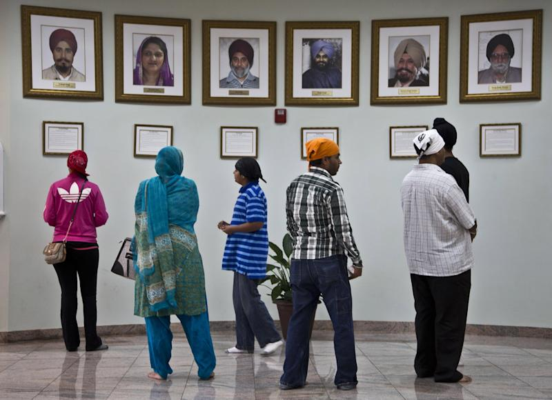 Visitors look at a memorial near the entrance of the Sikh Temple of Wisconsin Wednesday, July 31, 2013, in Oak Creek, Wis. Twelve months ago a white supremacist shot and killed six temple members, and the survivors plan to mark the one-year anniversary with solemn religious rites and a candlelight vigil. (AP Photo/Morry Gash)