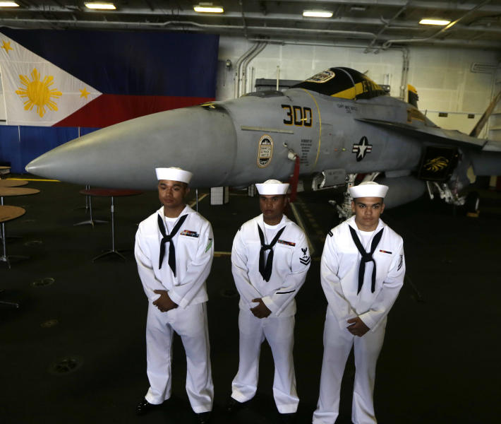 U.S. sailors of Filipino descent Marvin Balbuena, left, Ryan Regondola, center, and Spencer Rhoades pose in front of a US Navy FA-18 fighter jet and a giant Philippine flag as they are presented for the media during a tour of the U.S. Navy aircraft carrier USS George Washington, off Manila Bay in Manila, Philippines, Thursday Oct. 25, 2012. The U.S. aircraft carrier group cruised through the disputed South China Sea last Saturday in a show of American power in waters that are fast becoming a focal point of Washington's strategic rivalry with Beijing. (AP Photo/Bullit Marquez)