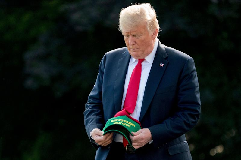 "President Donald Trump hold hats that read ""Make Our Farmers Great Again!"" as he walks across the South Lawn before boarding Marine One at the White House in Washington, Thursday, Aug. 30, 2018. (Photo: AP/Andrew Harnik)"