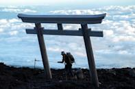 """Climbers at the summit can watch it breaking through the clouds behind a traditional """"tori"""" gate on the mountainside"""