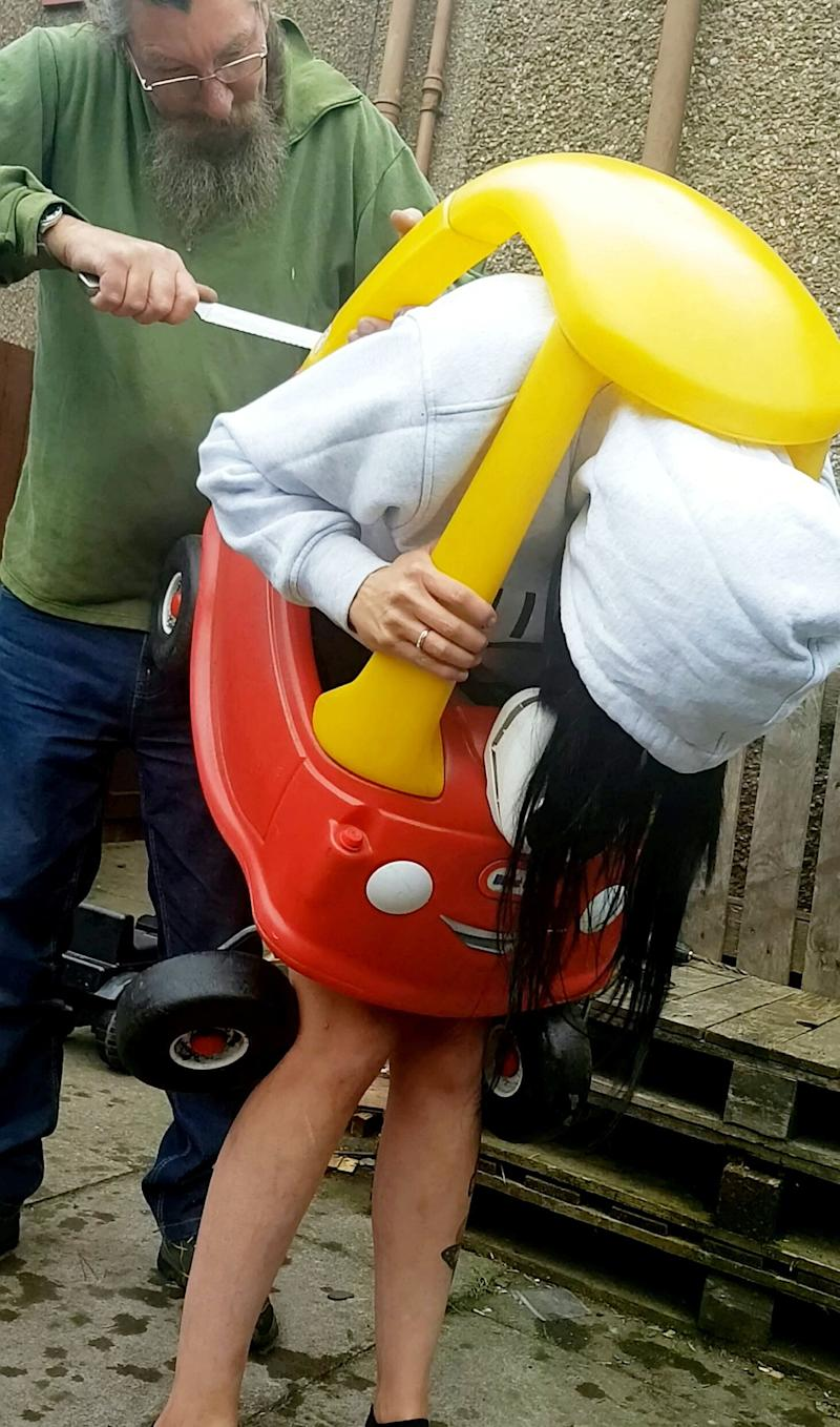 The 34-year-old's father had to cut her out of the toy car with a bread knife [Photo: SWNS]